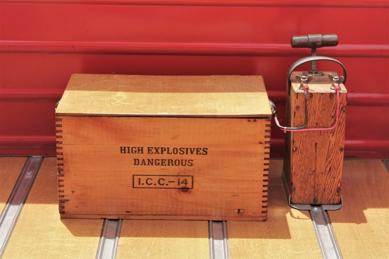 A wooden box containing explosives with a trigger