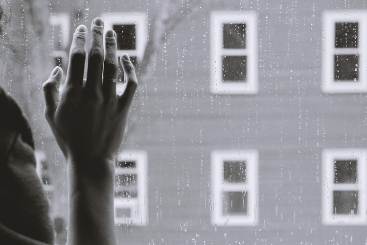 A greyscale photo of hand touching a window glass with rain drops on the exterior side