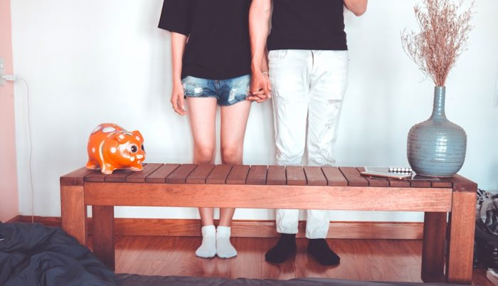 A couple standing holding hands in front of a coffee table