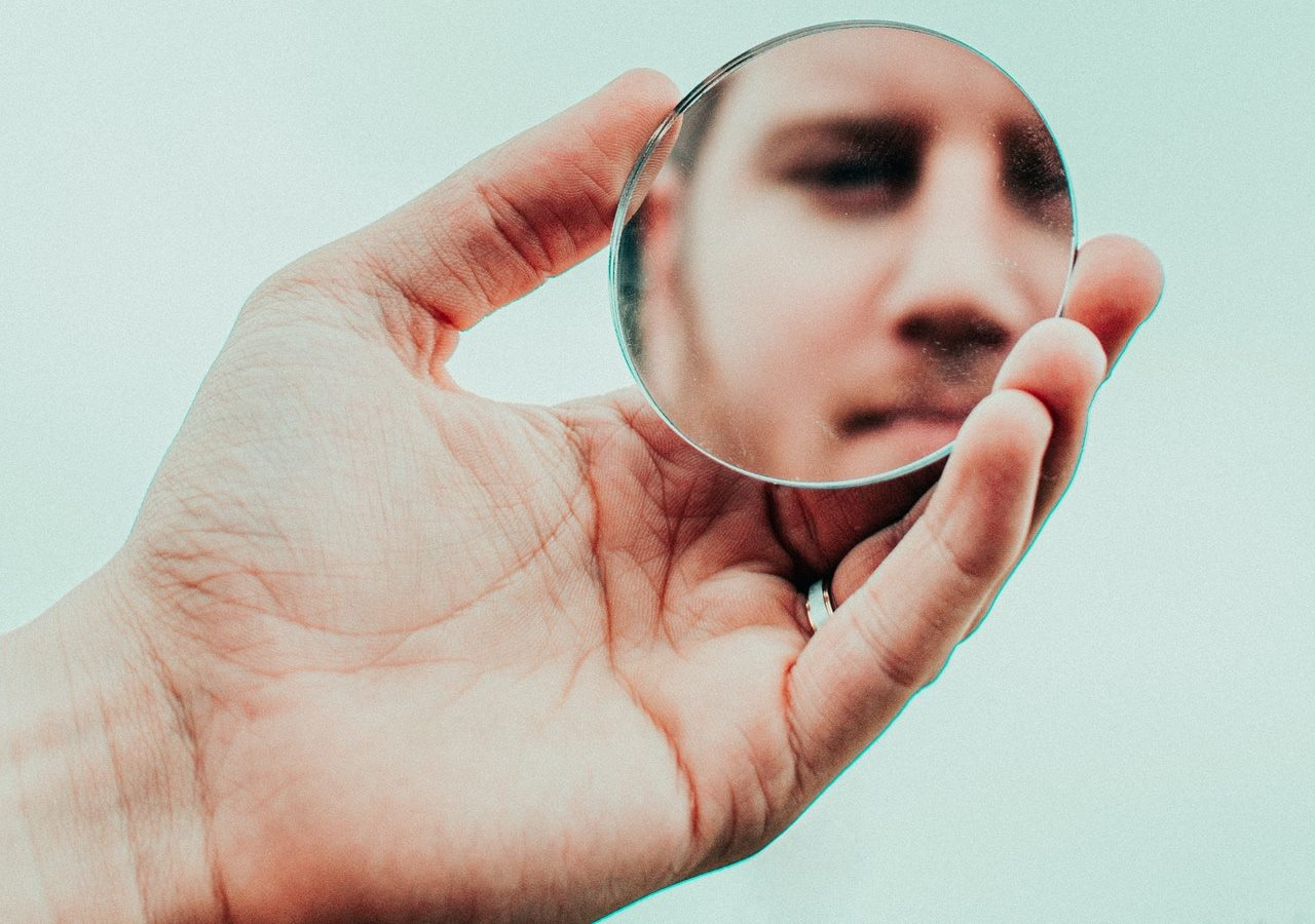 A man holding a small round mirror looking at himself