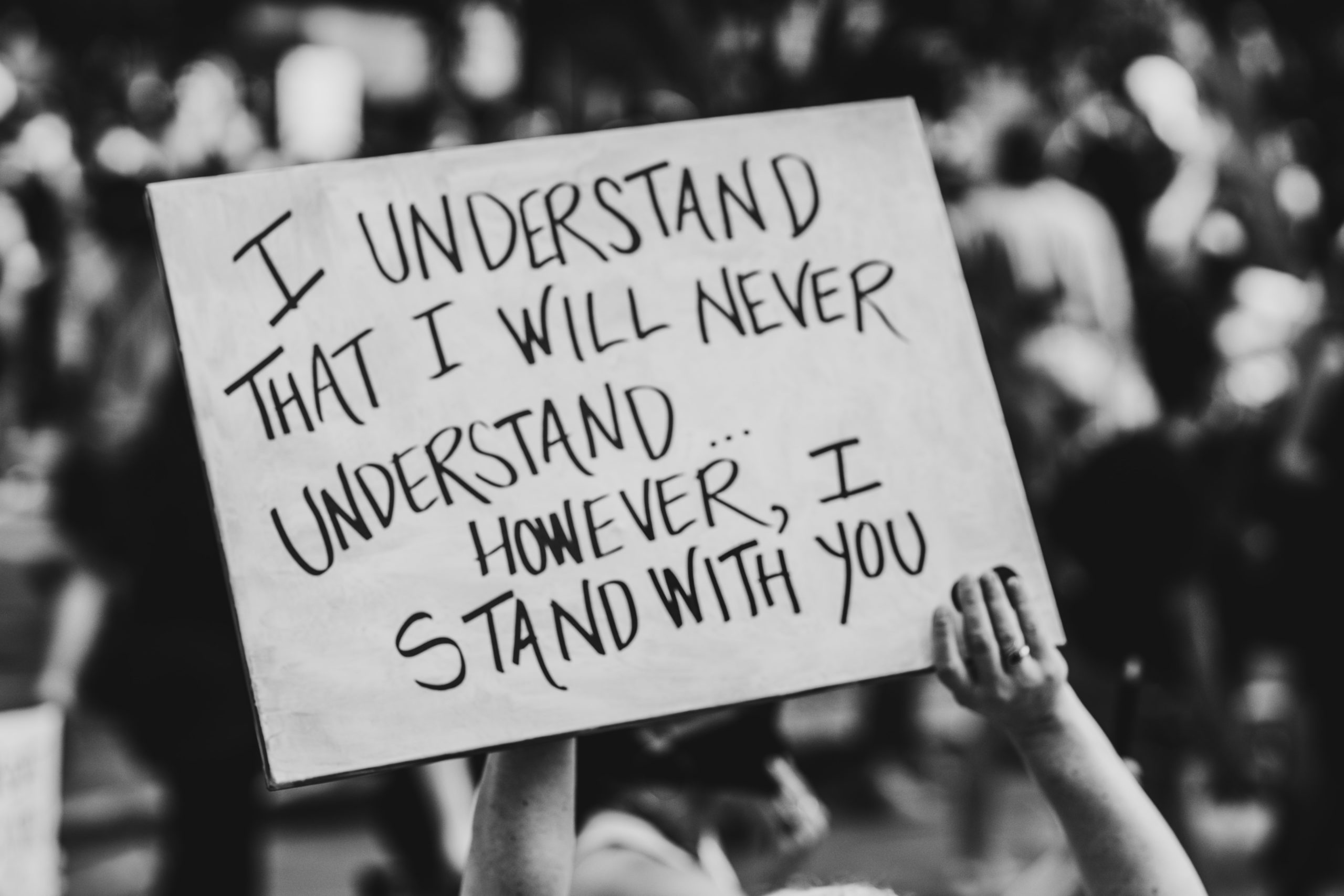 "A protest placard reads ""I understand that I will never understand, however, I stand with you"